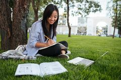 Beautiful asian student keeping records in paper notebook while Stock Image