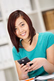 Beautiful Asian student texting on her mobile Royalty Free Stock Photo