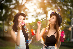 Beautiful asian teen girls blowing soap bubbles. Outdoor portrait Royalty Free Stock Photography