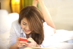 Beautiful Asian teen lay down smile with mobile ph Royalty Free Stock Image