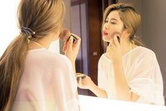 Beautiful Asian teenage girl applying powder her cheek before th Royalty Free Stock Image