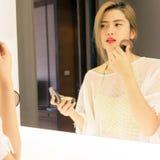 Beautiful Asian teenage girl applying powder her cheek before th Stock Image