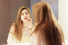 Beautiful Asian teenage girl touching her face before the mirror. In bathroom royalty free stock images