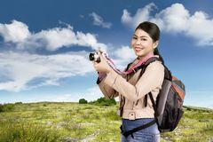 Beautiful asian tourist with bag using camera Stock Photography