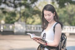 Beautiful asian tourist woman reading the travel guide book searching for for tourists sightseeing spot. Vacation travel in summer royalty free stock photo