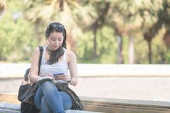 Beautiful asian tourist woman reading the travel guide book searching for for tourists sightseeing spot. Vacation travel in summer royalty free stock images