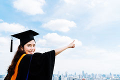 Beautiful asian university or college graduate student woman in graduation academic dress or gown, smiling and pointing at copy sp Royalty Free Stock Photography