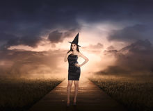 Beautiful asian witch woman with black hat. On the meadow Stock Photos