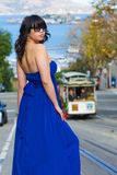 Beautiful Asian Woman. A beautiful Asian woman in a stunning blue dress on top of a San Francisco hill with a cable car approaching Royalty Free Stock Images