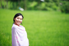 Beautiful Asian Woman on a Beautiful Day. Asian woman with her sarong at rice field shot with shallow DOF Royalty Free Stock Image