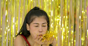 Beautiful asian woman blowing glitter confetti or pieces of silver foil in front of shiny shimmer curtain background. Slow motion stock footage