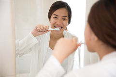 Beautiful asian woman brushing her teeth happily Stock Photos