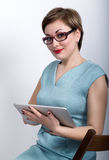 Beautiful asian woman in a business suit and glasses holds a pc tablet in the hands of and siting on a cheir Stock Photo