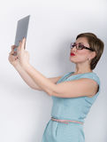 Beautiful asian woman in a business suit and glasses holds a tablet in the hands of Stock Images