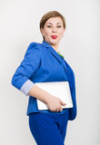 Beautiful asian woman in a business suit and glasses holds a tablet in the hands of Royalty Free Stock Image