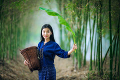 Beautiful asian woman carrying a basket and banana leaf looking. Forward hopefully Stock Photos