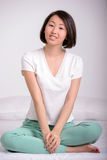 Beautiful asian woman. Charming asian girl sitting on the bed, on the background of room Stock Image