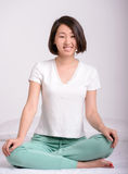 Beautiful asian woman. Charming asian girl sitting on the bed, on the background of room Royalty Free Stock Photography