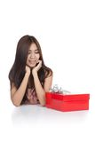 Beautiful Asian woman chin on hands  look at red gift box Stock Photography