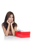 Beautiful Asian woman chin on hands with red gift box look away Royalty Free Stock Photo