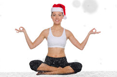 Beautiful asian woman in christmas hat with snow practicing yoga Stock Images