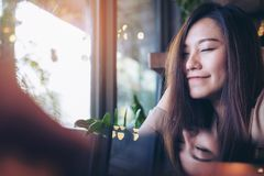 A beautiful asian woman close her eyes and enjoy relaxing time in modern cafe. With reflection on table Royalty Free Stock Photography