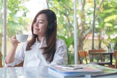 A beautiful Asian woman close her eyes and listening to music with headphone while drinking coffee with feeling happy and relax in Royalty Free Stock Photo
