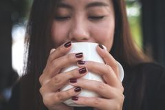 A beautiful Asian woman closing her eyes and holding a white cup of hot coffee with feeling happy in cafe. Closeup image of a beautiful Asian woman closing her Royalty Free Stock Photo
