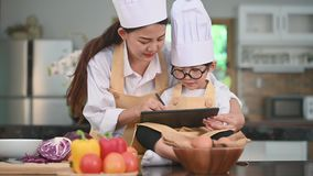 Beautiful Asian woman and cute little boy with eyeglasses prepare to cooking in kitchen at home with tablet. People lifestyles and