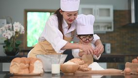 Beautiful Asian woman and cute little boy with eyeglasses prepare to cooking in kitchen at home together. Lifestyles and Family. H. Omemade food and ingredients stock video