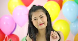 Beautiful asian woman dancing with colorful balloon background at the party in slow motion. stock video footage