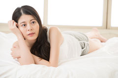 Beautiful asian woman daze and thinking lie on bed Stock Photography
