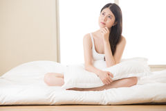 Beautiful asian woman daze and thinking in the morning. Beautiful asian woman daze and thinking sitting on bed in morning, bedroom background royalty free stock images