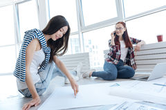 Beautiful Asian woman doing a drawing. Professional engineer. Beautiful young Asian women sitting on the floor and holding a pair of compasses while doing a Royalty Free Stock Image
