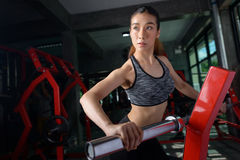 Beautiful Asian woman is doing exercises with the bar in the gym Royalty Free Stock Photography