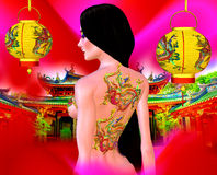 Beautiful Asian woman, dragon tattoo on her back, colorful makeup and bra. Long black hair with hanging gold lanterns against a colorful red background with stock photo