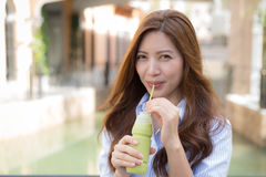 Beautiful Asian woman drink ice green tea Stock Photos