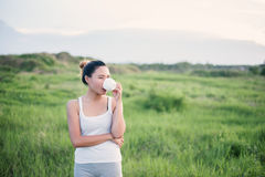 Beautiful Asian woman drinking coffee in meadows. Stock Images
