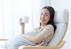 Beautiful Asian woman drinking coffee tea on a sofa by the windows. Beautiful Asian woman is drinking coffee tea on a sofa by the windows Stock Photography