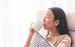 Beautiful Asian woman drinking coffee tea on a sofa by the wi. Beautiful Asian woman is drinking coffee tea on a sofa by the windows Royalty Free Stock Photography