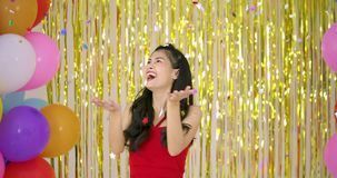Beautiful asian woman enjoy with confetti over gold glitter background. stock footage