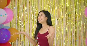 Beautiful asian woman enjoy with confetti over gold glitter background. Beautiful asian woman enjoy with confetti over gold glitter background, slow motion stock footage