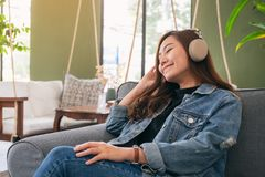 A beautiful asian woman enjoy listening to music with headphone royalty free stock photography