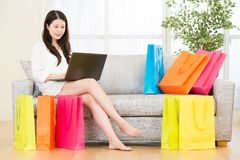 Beautiful asian woman enjoy online shopping with computer. Sitting on sofa colorful shopping bags around. indoor living room background Royalty Free Stock Photos