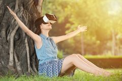 Beautiful asian woman enjoy VR headset glasses device. Beautiful asian woman enjoy virtual reality sitting on grass in outdoor park. VR headset glasses device Royalty Free Stock Image