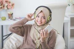 Beautiful asian woman enjoying music Stock Images