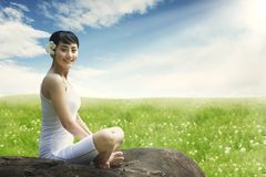Asian woman enjoying outdoors sitting on the rock at meadow against blue sky Royalty Free Stock Images