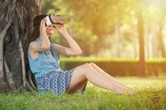 Beautiful asian woman experience VR headset glasses device. Beautiful asian woman experience virtual reality sitting on grass in outdoor park. VR headset glasses Royalty Free Stock Image