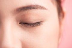 Beautiful asian woman eye with long eyelashes isolated on pink b. Ackground stock photos