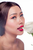 Beautiful asian woman face with perfect makeup with flowers of a Stock Image